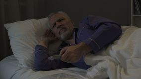 Annoyed senior man suffering insomnia and nervously switching TV channels. Stock footage stock video footage