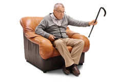 Annoyed senior man watching TV. Seated on an armchair isolated on white background Stock Photos