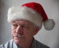 Annoyed senior with a Santa hat Stock Image
