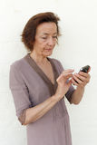 Annoyed senior woman texting. Senior woman annoyed with her smartphone, checking her social media or text Stock Image
