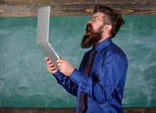Annoyed by slow internet. Slowly internet annoying him. Hipster teacher aggressive with laptop goes mad about slow speed. Internet connection. Teacher bearded royalty free stock images