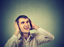 Annoyed stressed man covering ears, looking up, stop making loud noise stock photos