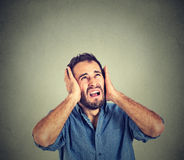 Annoyed, stressed man covering his ears, looking up, stop making loud noise. Portrait young annoyed, unhappy, stressed man covering his ears, looking up, to say stock photos