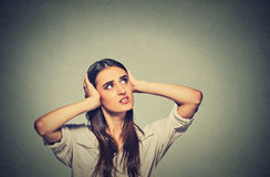 Annoyed stressed woman covering her ears, looking up loud noise stock image