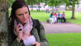 Annoyed student leaning against a tree making a phone call stock video footage