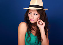Annoyed suspicious woman in straw hat lookig with hand near face Royalty Free Stock Images