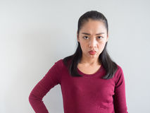 Annoyed and unhappy woman. Unhappy and annoyed face of Asian woman standing Royalty Free Stock Photo