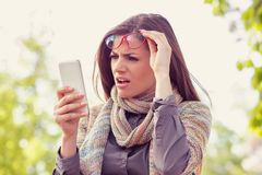 Annoyed upset woman in glasses looking at her smart phone with frustration while walking on a street. On an autumn day royalty free stock image