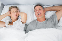Annoyed wife blocking her ears from noise of husband snoring. In bedroom at home Royalty Free Stock Images