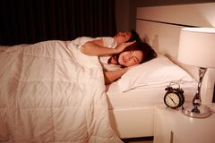 Annoyed wife blocking her ears from noise of husband snoring at. Annoyed young wife blocking her ears from noise of husband snoring at night Royalty Free Stock Images