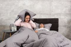 Annoyed wife blocking her ears by a pillow from noise of husband Stock Images