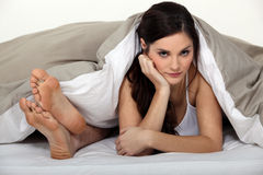 Annoyed woman in bed Stock Photography