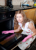 Annoyed woman cleaning the oven Stock Images