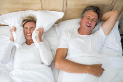 Annoyed woman covering ears with pillow while man snoring on bed Stock Photos