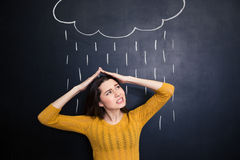 Annoyed woman covering head from rain drawn on chalkboard background Royalty Free Stock Image