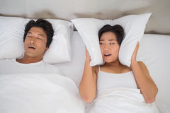 Annoyed woman covering her ears with pillows to block out snoring. Annoyed women covering her ears with pillows to block out snoring at home in bedroom Stock Photos