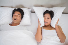 Annoyed woman covering her ears with pillows to block out snoring. Annoyed women covering her ears with pillows to block out snoring at home in bedroom Royalty Free Stock Images