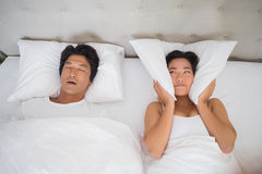 Annoyed woman covering her ears with pillows to block out snoring royalty free stock photos