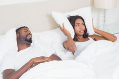 Annoyed woman covering her ears with pillows to block out snoring. Annoyed women covering her ears with pillows to block out snoring at home in bedroom Stock Images