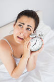 Annoyed woman holding an alarm clock in bed Stock Images