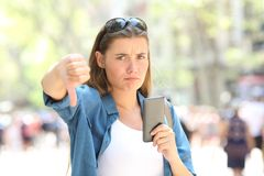 Annoyed woman holding a smart phone with thumbs down. Annoyed woman holding a smart phone looking at camera with thumbs down in the street Royalty Free Stock Photo