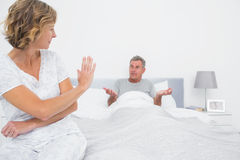 Annoyed woman looking at husband gesturing during a fight Stock Image
