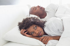 Annoyed woman lying in bed with snoring boyfriend Stock Photography