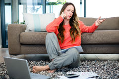 Annoyed woman making a phonecall. Annoyed woman sitting on the ground making a phonecall Royalty Free Stock Image