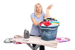 Annoyed woman standing behind an ironing board Stock Photography