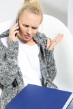 Annoyed woman talking on the phone Stock Photo