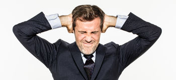 Annoyed young business man covering his ears from corporate burnout Royalty Free Stock Images