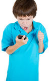 Annoyed young kid on mobile phone, yelling Royalty Free Stock Photo
