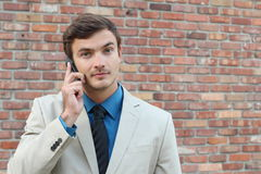Annoyed young male on the phone looking at camera Stock Photography
