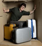 Annoyed young man feeling discomfort inside small room with luggage. I need more space concept. Full length portrait of irritated guy is sitting in confined Royalty Free Stock Photos