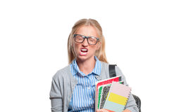 Annoyed young student girl holding books.  Back to school. Annoyed young student girl holding books, standing isolated on white background. Back to school Royalty Free Stock Images