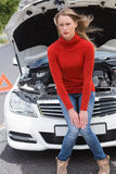 Annoyed young woman beside her broken down car Stock Image