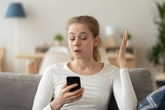 Annoyed young woman looking at smartphone having problem with phone royalty free stock photos