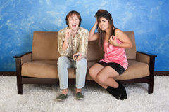 Annoyed Young Woman With Loud Boy. Laughing young men with headphones with distraught girl Royalty Free Stock Photo