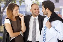 Annoying businessman celebrating with colleagues. Overly happy, annoying businessmen celebrating with startled female colleague after work, outdoors stock photo