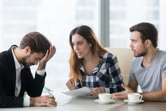 Annoying customers at meeting with realtor, financial advisor. Banker ask questions or argue. Tired embarrassed employee at meeting with young couple buying royalty free stock photography