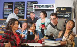 Annoying Nerd with Group. Mixed group of students annoyed with nerd in cafe Stock Photography