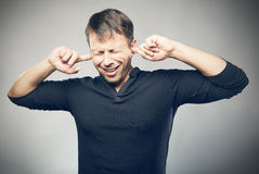 Annoying noise. The young man closed ears Stock Images