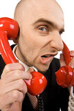 Annoying phone calls. A humorous image of a businessman talking simultaneously on two red phones, annoyed grimace on his face royalty free stock image