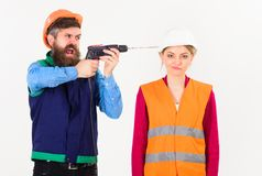 Annoying repair concept. Man with drill drills head of woman,. White background. Husband annoyed wife. Woman with bored face in helmet, hard hat. Builder royalty free stock images