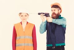 Annoying repair concept. Man with drill drills head of woman,. White background. Husband annoyed wife. Woman with bored face in helmet, hard hat. Builder stock images