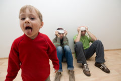 Annoying toddler. A view of an energetic and annoying toddler sticking his tongue out as adults sit in background with headaches royalty free stock photos