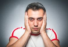 Annoying. Or worried young man over dark gray background royalty free stock image