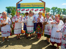 Annual agro exhibition SUMY-2013. SUMY, UKRAINE - AUGUST 17: Women wearing historical costume posing in traditional village background on annual agro exhibition Stock Photos