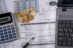 Annual budget, marketing research and business report with laptop, euro bills, coin and pen. On desk Stock Photos