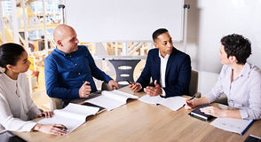 Annual general meeting between four educated and diverse individuals. Annual general meeting between four multiethnic, racially diverse male and female business Royalty Free Stock Photos